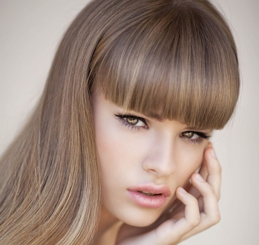Studio shot of young beautiful woman on light background. Professional make up.